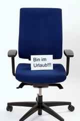"""Buerostuhl mit Zettel worauf steht:""""Bin im Urlaub"""""""