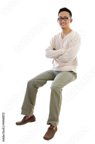 Full body Asian man sitting on a transparent block