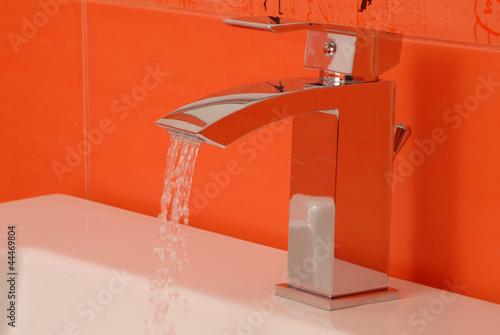 Хромированный водопроводный кран в ванной комнате.