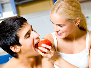 Cheerful couple eating apple together