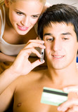 Couple with cell phone and plastic card, indoors