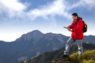 young man touching the  tablet pc on the top of mountain