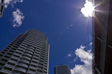 見上げた高層マンションと青空と太陽