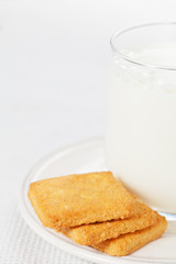 Glass of milk on the plate with cookies on the side