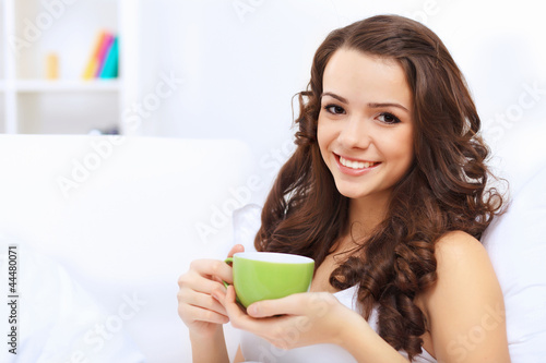 Young woman having cup of tea at home