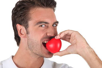 Man biting heart-shaped object