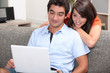 Couple watching film on laptop computer at home