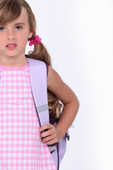 Little girl carrying backpack