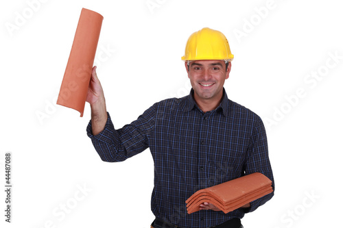Builder holding roof tiles