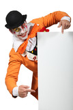 Man dressed up as a joker pointing to a board for your image