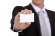 successful businessman holding business card