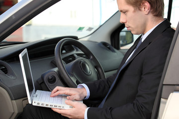Businessman using laptop in his car