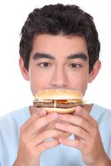 Young man facing a hamburger