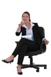young businesswoman sitting in a chair and pointing at you
