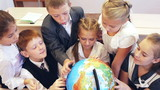 Happy schoolchildren searching country on the globe poster