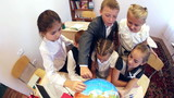 Happy schoolchildren learning geography in the classroom poster