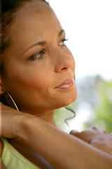 Head-shot of pensive brunette outdoors