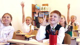 Adorable children raising their hands during the lesson