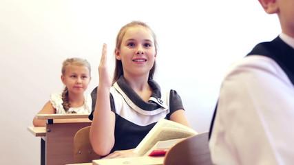 Adorable smart schoolgirl raising hand and giving answer