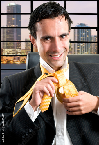 Businessman relaxed at office taking off his tie at night after