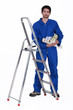 Man stood by ladder holding selection of wallpaper rolls