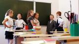 Schoolchildren standing near the blackboard and chatting poster