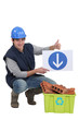Tradesman holding a sign pointing to a recycling bin