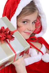 Glamorous child in a Santa's outfit offering a gift