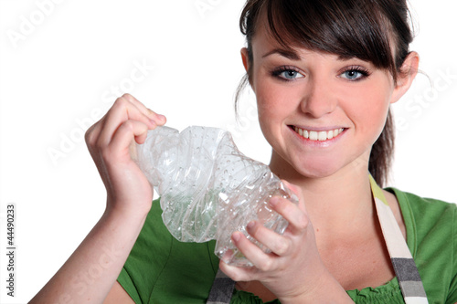 young girl squashing plastic bottle