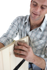 Furniture maker sanding wood