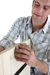 Furniture maker sanding wood