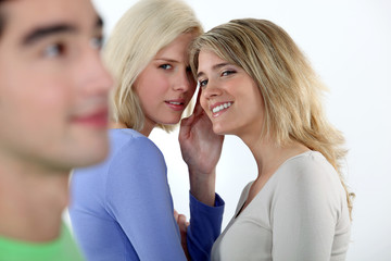 Young women gossiping about a man