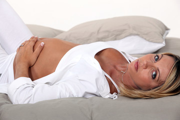 A pregnant woman laying in bed.