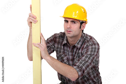 Man examining plank of wood