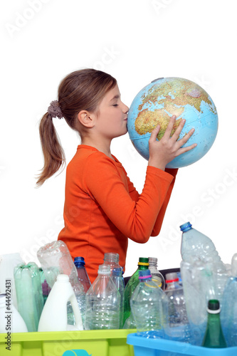 Little girl kissing planet earth next to her recycling
