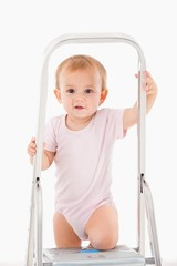 Adorable baby girl climbing on ladder