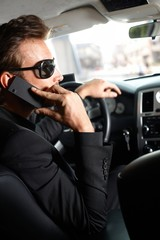 Young man on phone sitting in car