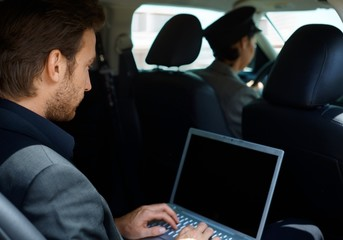 Young man in limousine using laptop computer