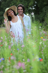happy young couple in high grass amid wild flowers