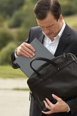 businessman gets the laptop from a business bag. Business concep