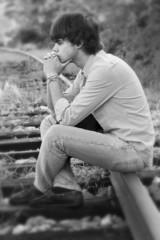 Joven pensativo, sentado en las vias del tren