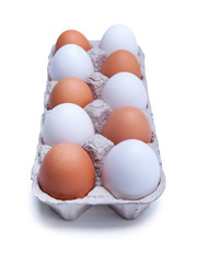 ten white and brown chicken eggs in a carton box, isolated