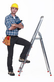 Portrait of a tradesman with his foot propped on a stepladder poster