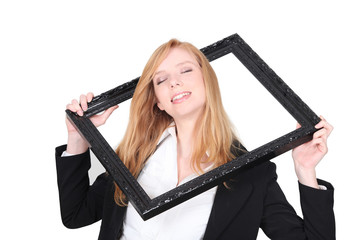 Pretty woman putting her head through a picture frame