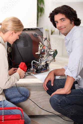 Couple repairing old television together