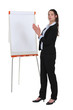 Brunette businesswoman stood by flip-chart
