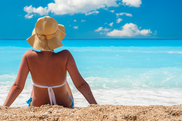 Woman sitting on the beach wearing sunhat
