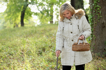 Middle-aged woman strolling through woods with basket