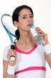 A tenniswoman taking a sip of water.