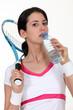 A tenniswoman taking a sip of water.